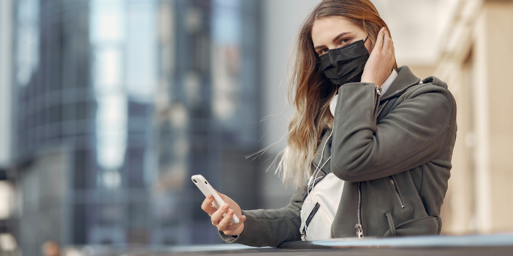Woman With Face Mask Holding Mobile Phone